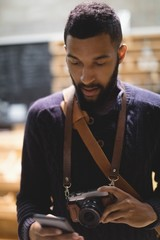 Young man with camera using mobile phone while standing in cafe