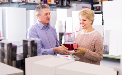 cheerful mature married couple in shopping center buys small kitchen household appliances