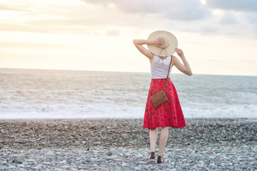 Girl in a red skirt and hat is standing by the sea, sunset. View from the back