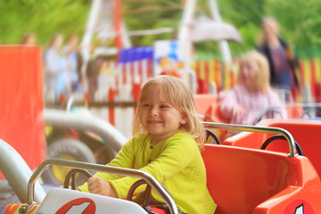 happy little girl on roller coaster ride in amusement park