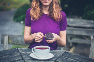 Woman with cup of tea and cupcake