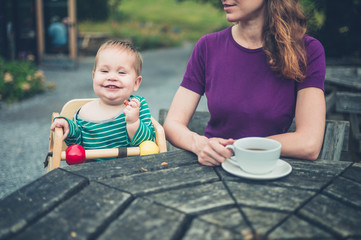 Mother and baby at table outside