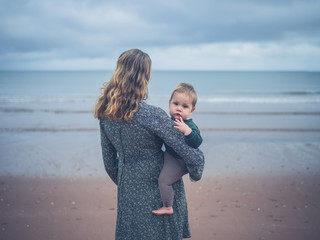 Young mother holding baby by the sea