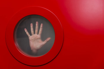 Female hand behind the glass of a round red porthole.Copy space