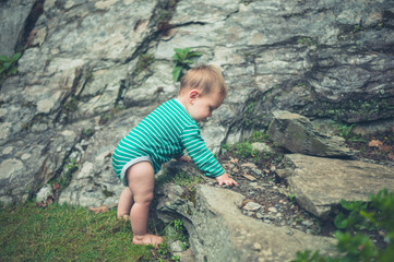 Little baby exploring nature by rocks