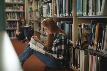 Female students reading book in library room