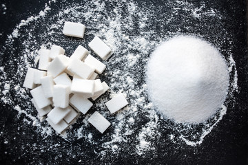 Unhealthy food concept - sugar  and flour on a black background. Dangerous high amount of sugar in food. Carbohydrates sources, top view.