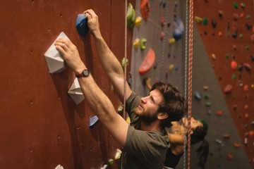 High angle view of confident athlete climbing wall in gym
