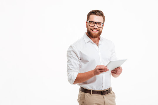 Happy young bearded man using tablet computer.