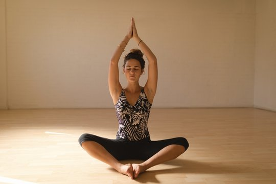 Young woman in prayer position meditating at studio
