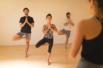 Yoga instructor guiding student in doing tree pose at studio