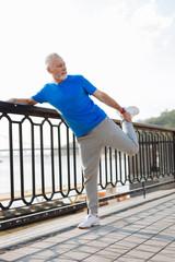 Fit senior man stretching on the bridge