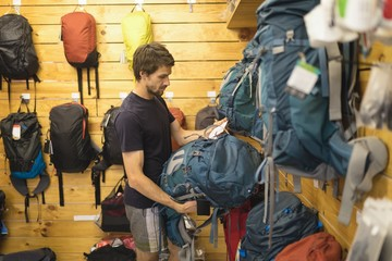 Young man examining bags in store
