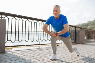 Senior man doing lunges during morning run