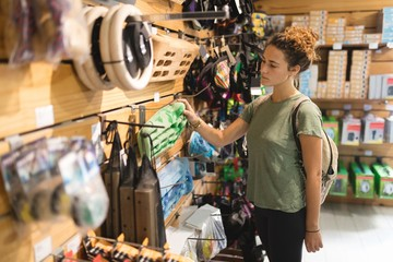 Woman examining sports equipment in store