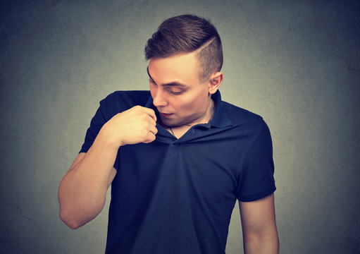 Man in awkward situation opening shirt to vent isolated on gray background. Human emotions facial expression