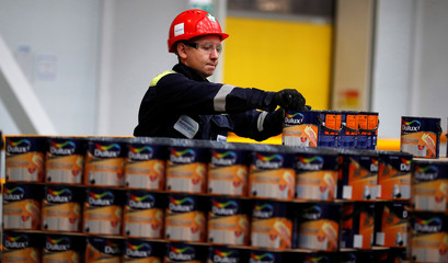 A worker moves empty Dulux paint cans as they wait to be filled inside AkzoNobel's new paint factory in Ashington, Britain