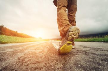 Close up image traveler feet on asphalt road in sunset time