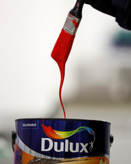 Paint drips from a paint brush into a can of Dulux paint inside AkzoNobel's new paint factory in Ashington, Britain