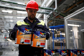 A worker checks empty Dulux paint cans as they wait to be filled on the production line inside AkzoNobel's new paint factory in Ashington, Britain