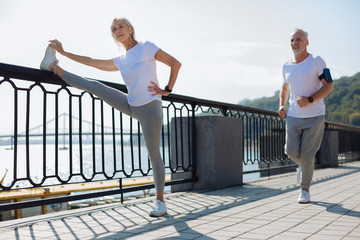 Fit woman doing stretching exercises while man jogging