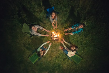 The five people hold hands near the bonfire. night time, view from above