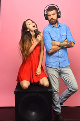 Couple in love sits on the loudspeaker on pink background