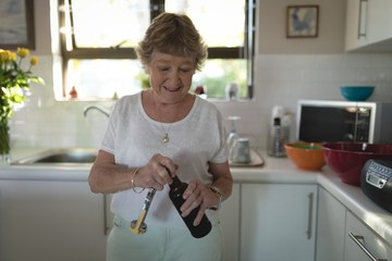 Senior woman removing lid of wine bottle