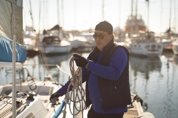 Yachtsman adjusting the rope tuning