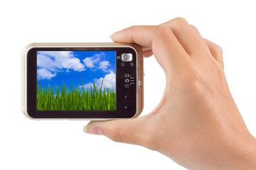 Hand with camera and Grass and cloudy sky (my photo)