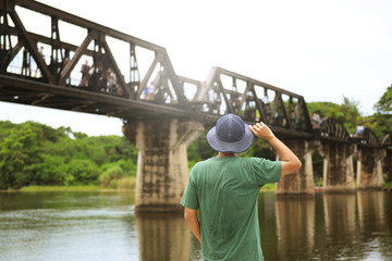 Man tourist is traveling at Kanchanaburi and watching history of World War 2, The bridge on the River Kwai.
