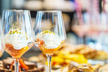 Dessert in Glass with Whipped Cream, Orange and Pistachio, Close-up View