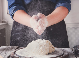 Woman baker knead and sprinkle yeast dough with eggs and flour