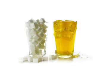 glass full of sugar cubes compared to a glass with a yellow sweet beverage, isolated on a white background