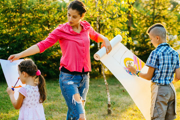 Happy mother holding roll with paper and helping two her kids painting in the park. Art, drawing and kids creativity concept.