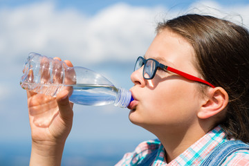 Young girl drinking water outdoors