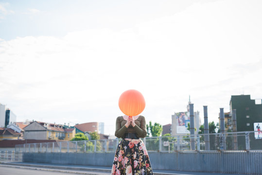 oung woman beautiful outdoor playing with balloon covering face - childhood, girl power, happiness concept