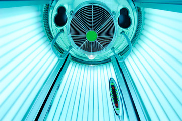 An empty solarium for sunbathing in a beauty salon or a spa with included ultraviolet lamps