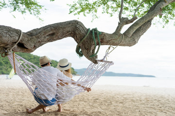 couple spent time on vocation on the beach, sitting together on hammock
