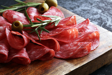 thinly sliced salami on a wooden cuttingboard