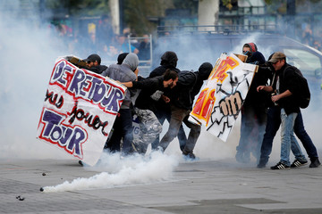 Demonstrators run through a cloud of tear gas during a national strike and protest against the government's labour reforms in Nantes
