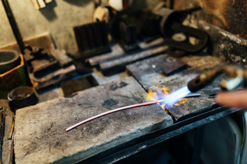 Jeweler processing metal bar
