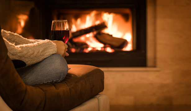Young woman sitting at home by the fireplace and drinking a red wine.