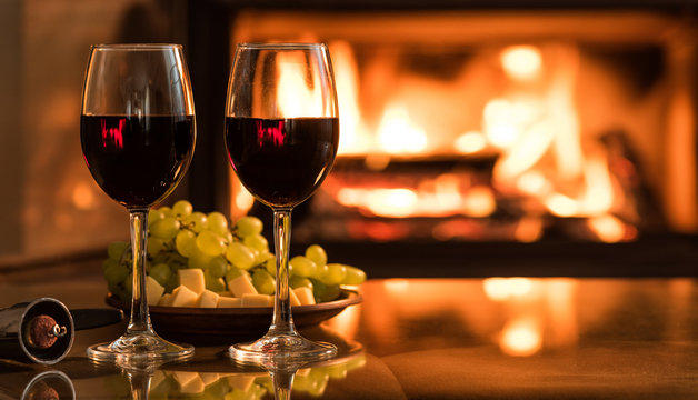 Two red wine wineglasses over fireplace background.