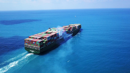 Mega huge fully loaded container ship at sea aerial top down