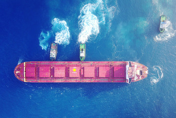 Large bulk carrier ship pulled by tow-three  tugboats in the port