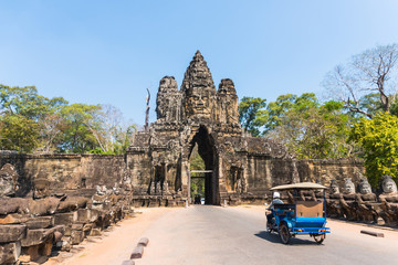 Tuk tuk and angkor thom gate in siem reap cambodia