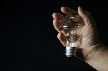 bulb light in human hand and black background