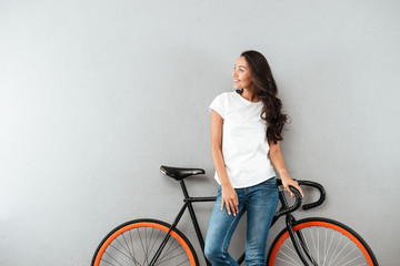 Smiling pretty asian woman leaning on a bicycle