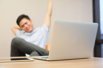 blurred soft focus on laptop computer with asian employee man stretching his body for relaxing after work hard , healthy people concept